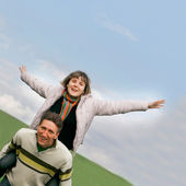 Young couple having fun on sky background — Stock Photo