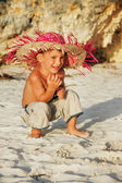 Happy boy sitting on sand beach — Stock Photo