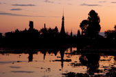Buddha statue and temple during sunset on a lake — Stock Photo