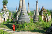 Young monk walkng between stupas — Stock Photo