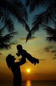 Anne ve oğlu günbatımı, tropikal silueti — Stok fotoğraf