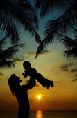 Silhuett av mor och son i solnedgången i tropikerna — Stockfoto