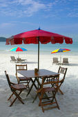 Wooden table and chairs on beach — Stock Photo