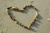 Heart from seashells on sand beach — Stock Photo
