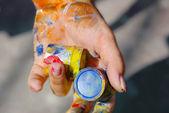 Mano femenina con tubos de color — Foto de Stock