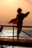 Silhouette of girl dancing with scarf — Stockfoto