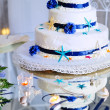 Wedding cake with bouquet and stemware — Stock Photo