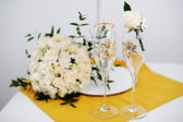 Wedding glasses and groom boutonniere — Stock Photo