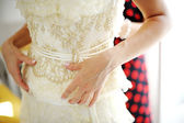 Bridesmaid helping bride to dress — Stock Photo