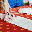 Stock Photo: Bride signing marriage license or wedding contract