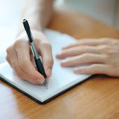 Male hand writing on a notebook — Stock Photo