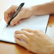 Student hand with a pen writing on notebook — Stok Fotoğraf #29324395