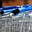 Row of metal shopping carts in a supermarket — Stock Photo