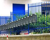 Row of gray metal mailboxes near railing — Stock Photo