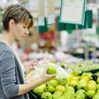 Woman choosing apple at fruit supermarket — Stock Photo
