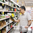 Man shopping and looking at food in supermarket — Stock Photo #34589849
