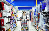 Woman looking at household items in supermarket — Stock Photo