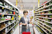Woman shopping and choosing goods at supermarket — Stock Photo
