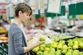 Woman choosing apple at fruit supermarket — Stok fotoğraf