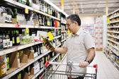 Man shopping and looking at food in supermarket — Stock Photo