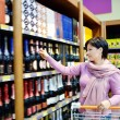 Woman shopping and choosing liquor at supermarket — Stock Photo