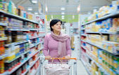 Woman pushing shopping cart looking at goods in supermarket — Stock Photo