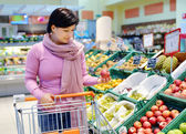 Pretty woman choosing apple at fruit supermarket — Stock Photo