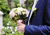 Groom hands holding wedding bouquet — Stock Photo