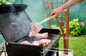 Man at a barbecue grill preparing meat for a garden party — Stock Photo