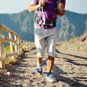 Hiker with backpack running on a path of mountain — Stock Photo