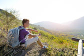 Hiker with backpack relaxing on a path of mountain — Stock Photo