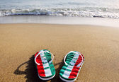 Flip flops with the word Italy on beach sand - holidays and relaxation concept — Stock Photo