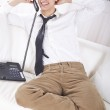 Young businessman sitting on couch talking on phone, smiling. — Stock Photo