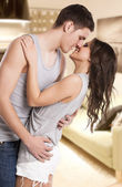 Passionate couple kissing in the living room — Stockfoto