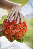 The couple Hands on the Bridal Bouquet — Stock Photo