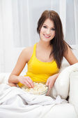 Young woman eating popcorn and watching TV at home — Stock Photo