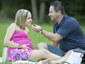 Happy pregnant couple at beautiful sunny day in park — Stock Photo