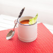 Tomato soup on a red cloth with a spoon — Stockfoto