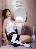 Drunk woman sitting dizzy on the toilet floor — Stock Photo