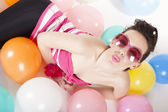 Party girl lying with balloons on the floor in colourful clothes — Stock Photo