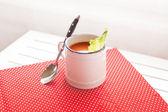 Zuppa di pomodoro su un panno rosso con un cucchiaio — Foto Stock
