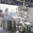 Stock Photo: Chef cooking at commercial kitchen - hot job