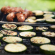 Sausages and vegetables on grill — Stock Photo