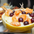 Melon stuffed with melon pieces, tangerine and grapes — Stock Photo