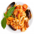 Pasta with tomato sauce and seafood in plate — Stock Photo