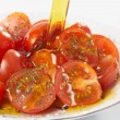 Olive oil being poured on spicy tomatos — Stock Photo #12474526