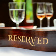 Reserved plate on a restaurant table - Stock Photo