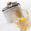 Stainless steel hip flask and glass of whisky — Stock Photo