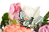Natural flowers with artificial butterfly — Stock Photo