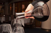 Waiter pouring red wine from decanter — Stock Photo